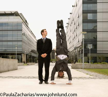 Business Man of Hispanic descent doing a handstand with another man standing next to him. Office buildings in the background.